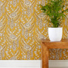 Floral stems of Muscari grow among Echinacea and meandering leaves on a mustard color wallpaper.
