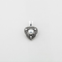 Burnished silver pendant with a white shell pearl centre and tribal detail