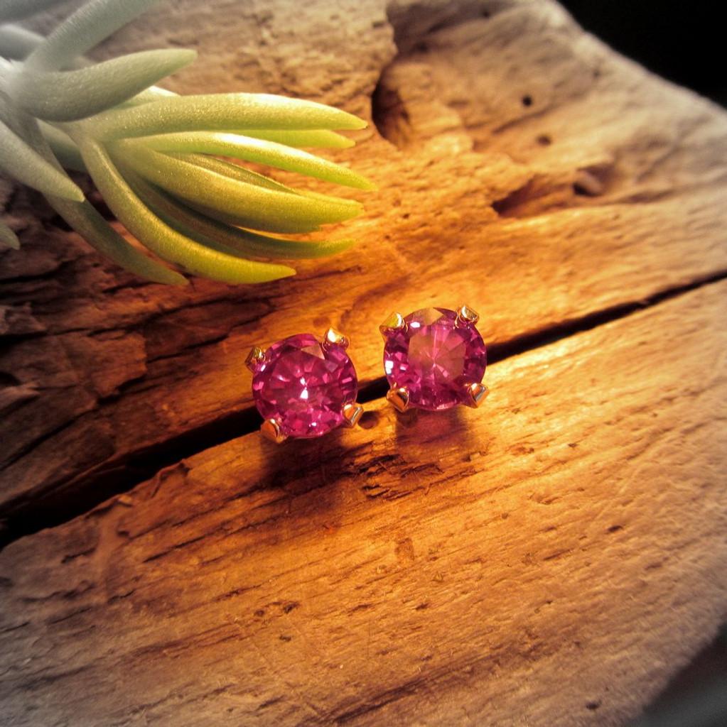Lab grown real Alexandrite stud earrings under incandescent light