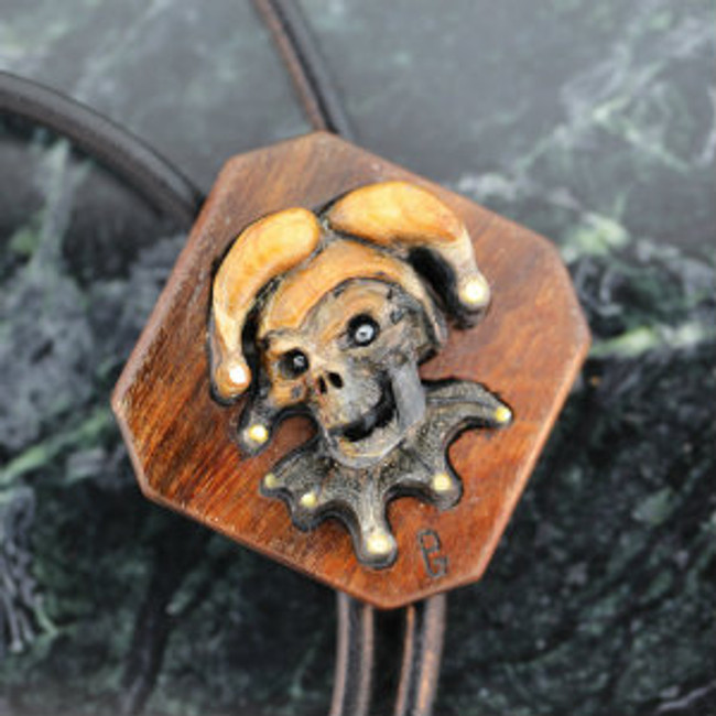 Bolo. Picasso marble carving of a Court Jester Skull. Hematite eyes. Leather cord. Gold pearl bell tips on Jester. Mounted on Tigerwood. Tigerwood tips with hematite ends.