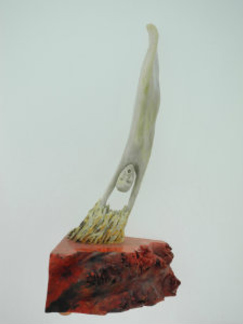 """Descending Soul"".  Deer antler carving of a soul descending into hell. Mounthe on a piece of stabilized (with red dye) California buckeye burl wood. 6.5"" X 3.25""."