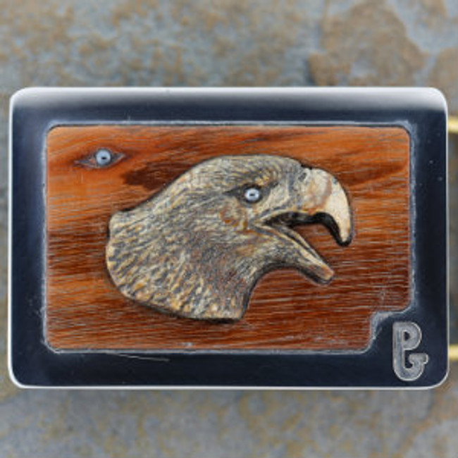 """""""The Double Eagle"""". An eagle head carved from Picasso marble by Paul Grussenmeyer. Hematite eye in carving and on eagle emerging from the Tigerwood grain in the background. Mounted in Paul's signature series stainless steel belt buckle."""
