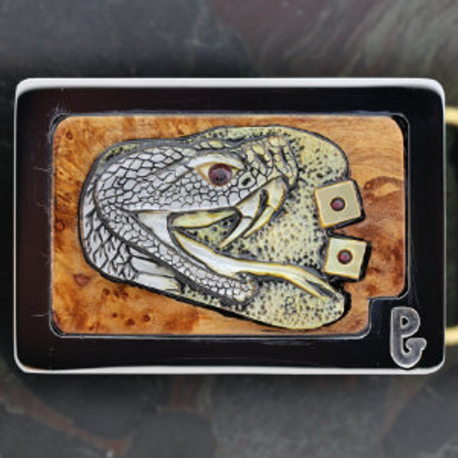 """Belt buckle with carved gold lip mother-of-pearl rattle snake head and """"Snake Eyes"""" roll of the dice. Set in burl wood and mounted in Paul's signature series stainless steel belt buckle."""