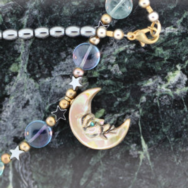 Paul Grussenmeyer carved moon face on abalone, necklace features hematite oval beads & stars. fluorite multi-colored round beads, plus gold plated beads and lobster claw clasp.
