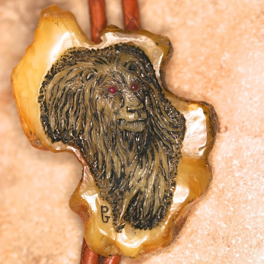 Bolo.  African Lion carved on Amber. Ruby eyes. Leather cord. Natural claw tips.