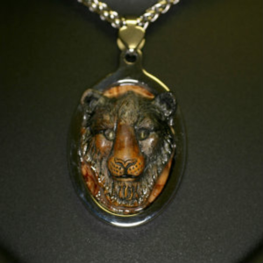 """Paul Grussenmeyer carved Picasso marble lion with exotic wood background, tiger eye stone eyes, mounted in stainless steel frame pendent and hung on 24"""" stainless steel necklace with toggle clasp."""