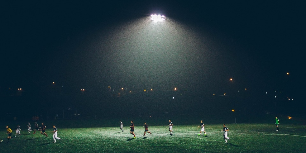 A bright floodlight illuminates a soccer game at night
