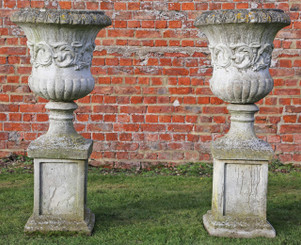 Pair of classical antique cast stone planters urns on plinths