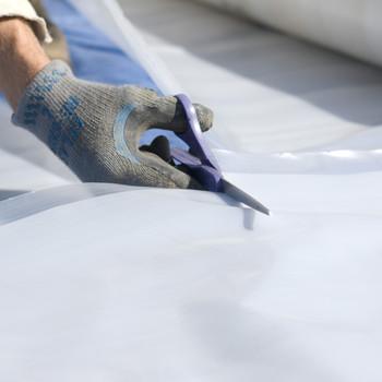 Scissors Cutting Through Greenhouse Plastic