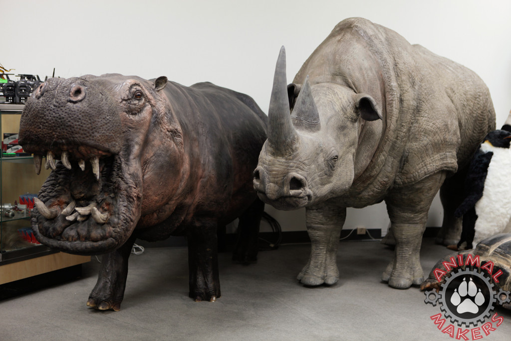 hippopotomus replica standing next to a rhino replica