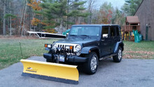 Homesteader snow plow installed on a Jeep