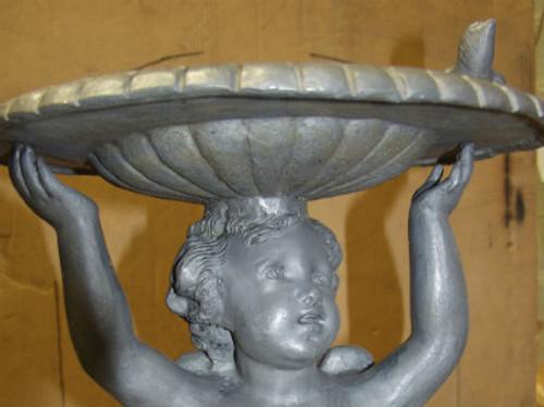 Cupid holding a birdbath shell