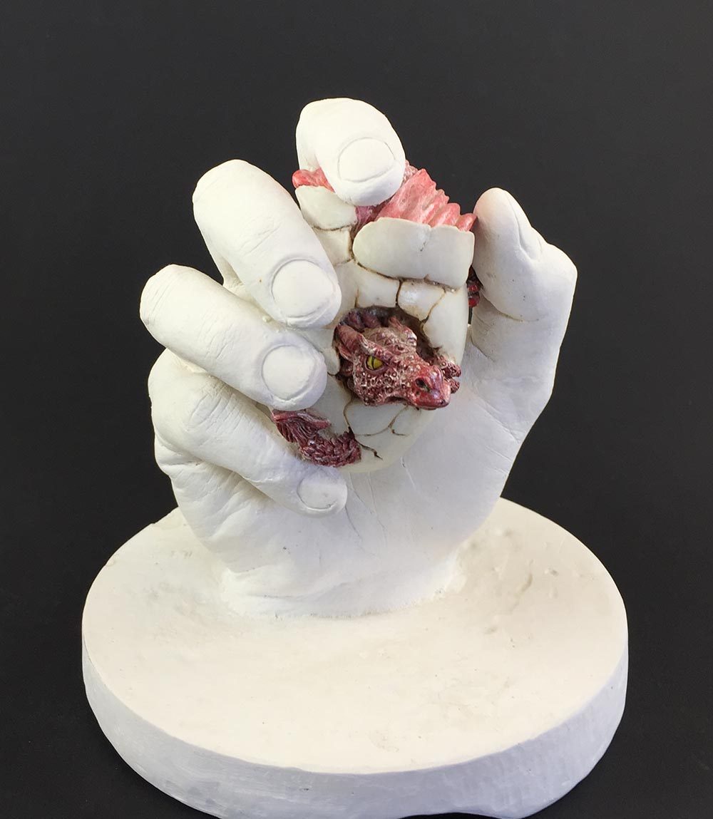 It is quite easy to hold an object while making a hand mold with alginate. Just leave the object behind in the mold when you remove your hand and the object will be there when the casting is finished