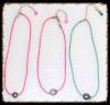 Tahitian pearls on Colored cords.  Round on pink cord with extender chain.