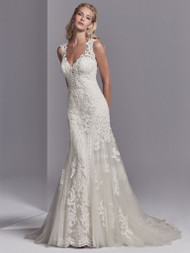 Sottero and Midgley Channing Rose. This wedding dress features striking lace motifs accented in beading atop tulle. Embroidered lace borders the tulle on either side of the fit-and-flare skirt. Featuring an illusion plunging sweetheart neckline, illusion straps, and an illusion open back, all accented in lace motifs. Lined with shapewear for a figure-flattering fit. Finished with covered buttons over zipper closure. Available in: Ivory, Ivory over Pale Blush, shown.