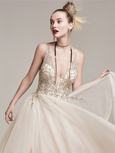 Sottero and Midgley Amelie.  Dione organza creates the dramatic Amelie ball gown with horsehair layered skirt, featuring a breathtaking bodice adorned with Swarovski crystals and pearls, plunging illusion V-neckline and back. Finished with crystal buttons over zipper closure. Available in White, Ivory, and Champagne.