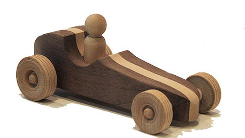 "This sporty little race car is modeled after the lightning fast vehicles that ran in the Indianapolis 500 during the 1950s, with a contrasting wood racing stripe down the center. Although not quite as fast, it is smartly engineered and equally irresistible to dreamers young and old. Hand crafted in different combinations of cherry, walnut, maple and oak, it is 8"" long x 3"" high x 2"" wide."