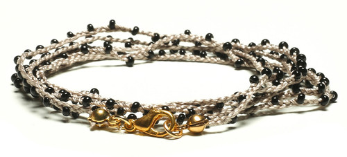 "32""  braided off white silk thread necklace with black seed beads and gold plated clasp."