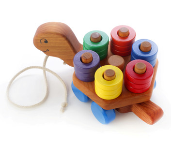 Give me a spin! Our newest wooden pull toy is a stacker, too. When pulled along, the hexagon-shaped stacker spins making a rainbow of color. The faster you pull, the faster it spins! Includes 18 removable choke-safe wooden rings.