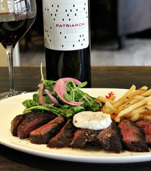 Marinated sirloin steak, chargrilled and served with grilled tomatoes, onions, pepper salad, hummus, pita and steak fries.
