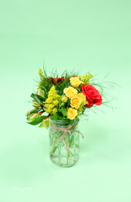 red and yellow wedding centerpiece. mixed fresh flowers arranged in a mason jar