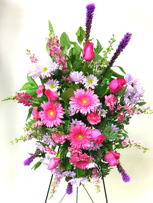 A Bright mix of pinks and purples designed in a standing sympathy easel. A mix of bright Gerberas, roses, and unique mixed flowers.