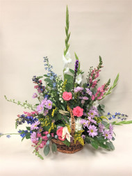 Mixed Wildflower sympathy tribute designed in a basket. A variety of color and fresh flowers, this piece is a great sympathy tribute