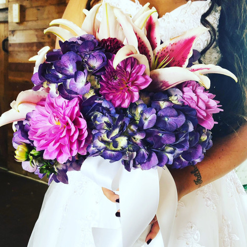 A Beautiful fresh purple mix! Local Grown Lilies, purple hydrangea, this Bridal Bouquet is absolutely stunning! Designed locally at Earle's Loveland