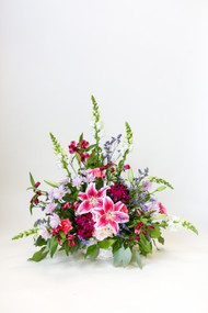 The Graceful Lady Sympathy One sided arrangement with local grown stargazer lilies. A vibrant pink display with accent colors and mixed fresh flowers.