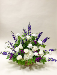 Neutral fresh cut long stemmed premium roses and clustered Hydrangea accented with purple and blue hues of mixed fresh cut flowers arranged in a woven basket.