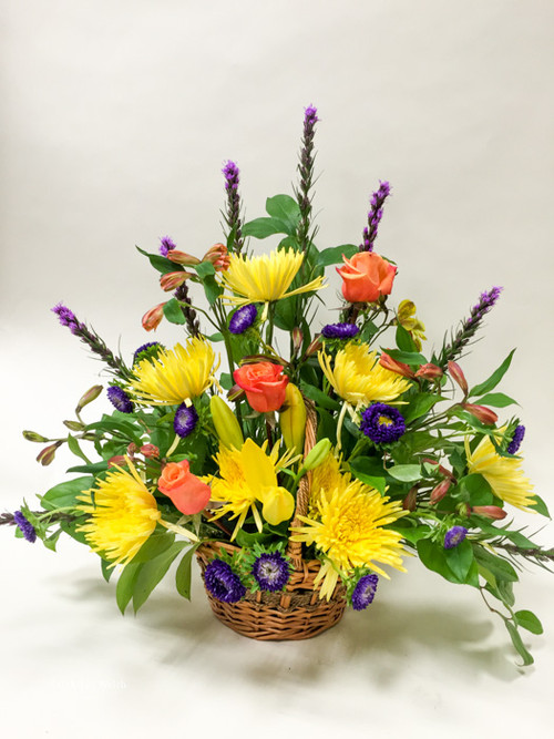 Vibrant yellow orange and purple Burst of Sunshine Sympathy one sided basket sympathy arrangement.