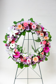 Premium Pink Sympathy Tribute Wreath made with a mix of local grown white lilies, vibrant pink Gerbera daisies, and other mixed fresh cut flowers in accent colors.