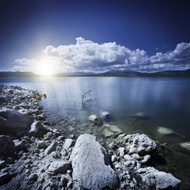 Tranquil Lake And Rocky Shore With Sun Over Horizon Sardinia Italy