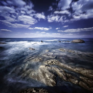 Rocky Shore With Tranquil Sea Against Cloudy Sky At Sunset Sardinia Italy