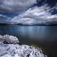 Tranquil Lake By Rocky Shore Against Cloudy Sky Sardinia Italy