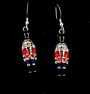 Get in the holiday spirit with these beautiful nutcracker charm silver earrings. Each little soldier measures 1.3 inches tall by 0.4 inches wide, with exquisite detailing both front and back, On silver French wires with high gloss red, blue and black enamel.