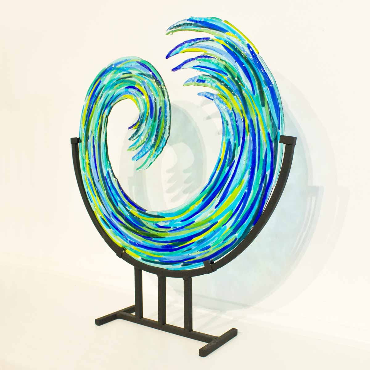 Hand-crafted glass art by Galiani Glass Art. Free-standing kilnformed glass wave standing on matt black heavy metal stand (optional).