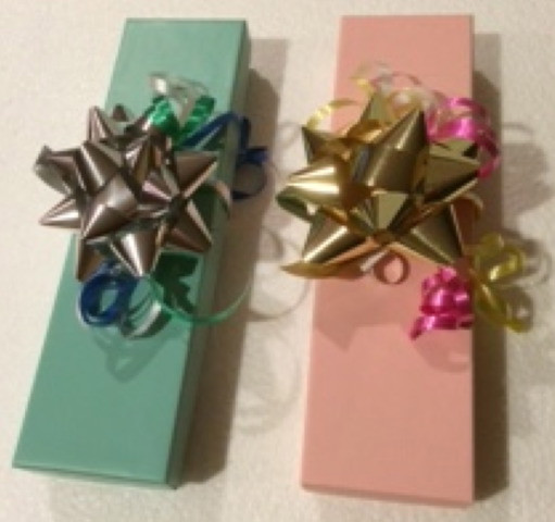 Two sturdy gift boxes with a pad of soft cotton on the inside hold 1-2 dozen personalized pencils.  Includes a three colored ribbon and gift bow.  Available in light blue or light pink.