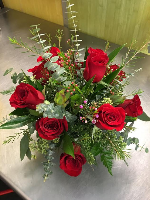 A dozen red roses in a clear glass cube