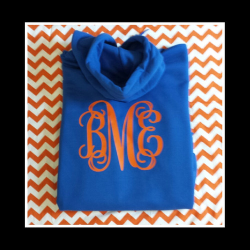 A monogrammed hooded crewneck sweatshirt with the double pocket in the front.  This monogram is positioned on the front middle area.