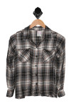 front of top has button up closure with two breasted pockets, collar, long sleeves and plaid material with black, white and blue colors in it.