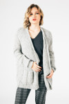 front shows long sleeve cardigan in light heather grey paired with dark grey tee and grey & black plaid leggings.