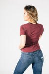 back view shows jeans with 2 back pockets with sight distressing on right back pocket and back of light burgundy tee.