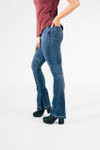 side view shows denim in light to medium blue denim color with boot cut fit and slit at bottom hemline.