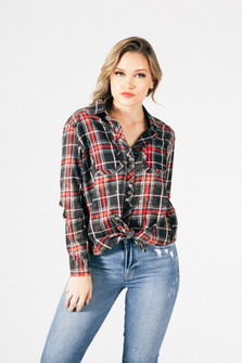 front of blouse shows tied bottom with button up front, long sleeves and plaid colors in dark grey, red, black and white.