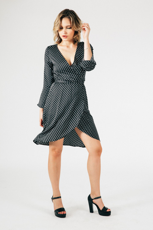 front shows long bell sleeves with front deep V-neckline and wrap front in black and white polk-a-dot print. Length hits above knee.