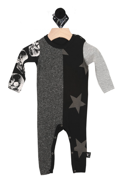 front of onesie shows quilted fabric look with half of body heather grey and other half black with grey stars. left arm sleeve is white and right arm sleeve is black with white skull print. snap closure at left shoulder and bottom