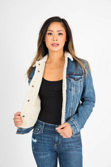 front of jacket shows model showing inside ivory sherpa lining with denim outside.