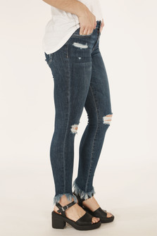 side view of jeans show holes at both knees and distressing at right pocket.
