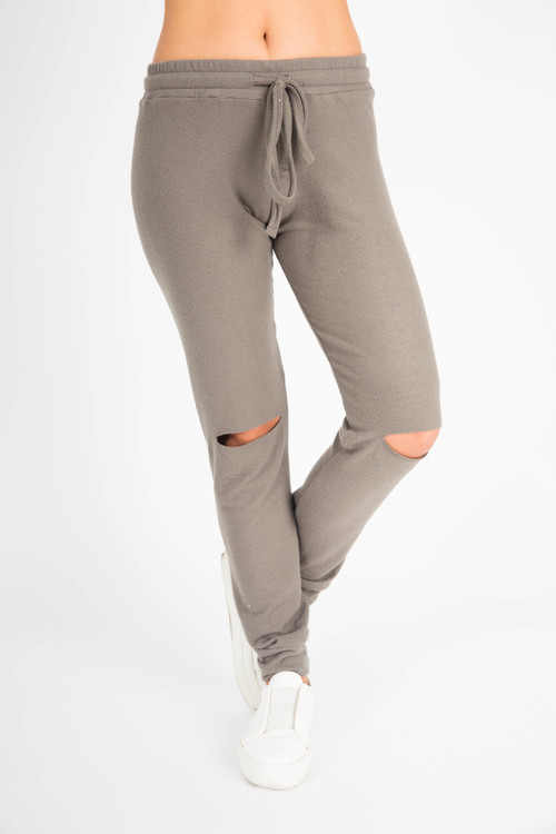 pants show elastic waistband with drawstring, slits at both knees and cuffed ankles in grey/green  color.